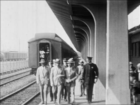 vidéos et rushes de rudolph valentino in suit walking with other men at train station / newsreel - prelinger archive