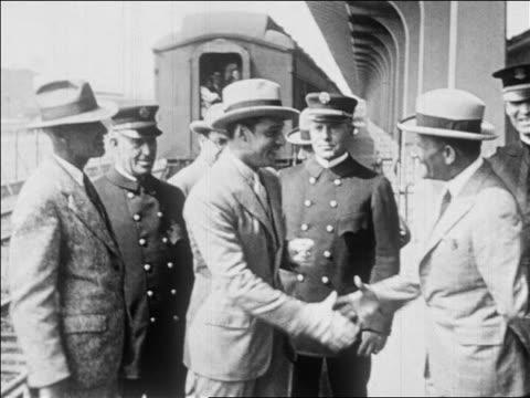 vídeos de stock e filmes b-roll de rudolph valentino in suit shaking hands with other men at train station / newsreel - 1926