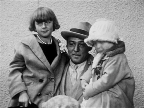 b/w 1926 tilt down rudolph valentino in hat posing with 2 little girls boy / newsreel - anno 1926 video stock e b–roll