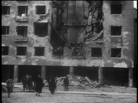 vídeos de stock, filmes e b-roll de b/w 1939 tilt up people walking in front of bombed building after german invasion / warsaw / documentary - polônia