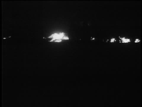 SILHOUETTE people walk in front of fires at night after German bombing / Warsaw / doc