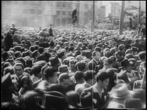 vidéos et rushes de tracking shot mob in piazza del duomo pushing to see bodies of mussolini + henchmen / milan / newsreel - execution
