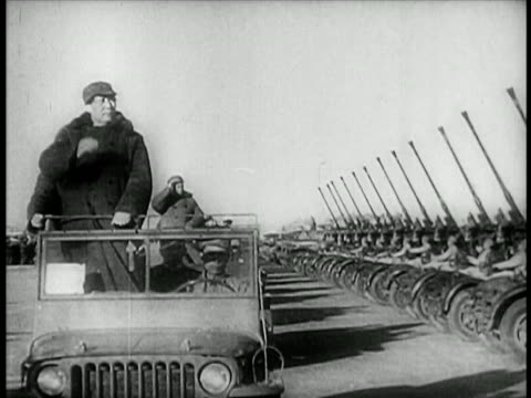 mao zedong in off-road vehicle riding past row of tanks + saluting / china / educational - mao tse tung video stock e b–roll
