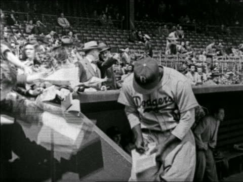 B/W 1940s Jackie Robinson signing autographs for children in ball park