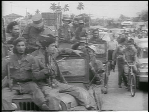 Fidel Castro smoking cigar rides in offroad vehicle with other soldiers / postrevolution Havana