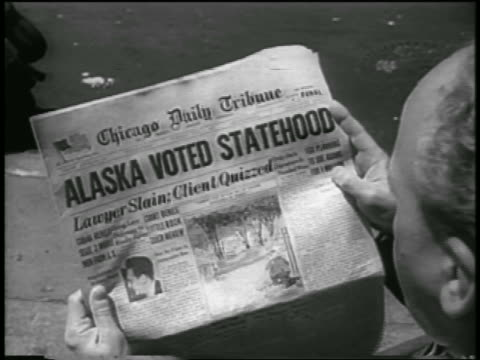 """over-the-shoulder man looking at newspaper with """"alaska voted statehood"""" headline / newsreel - 1958 stock videos & royalty-free footage"""