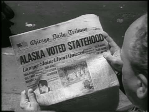 vídeos de stock e filmes b-roll de b/w 1958 overtheshoulder man looking at newspaper with alaska voted statehood headline / newsreel - escrita ocidental