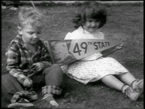 vídeos de stock e filmes b-roll de b/w 1958 boy girl sitting on grass / girl holding alaska 49th state pennant / newsreel - alasca