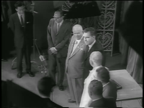 b/w 1959 high angle richard nixon nikita khrushchev others posing under lights in room / moscow - 1959 stock-videos und b-roll-filmmaterial