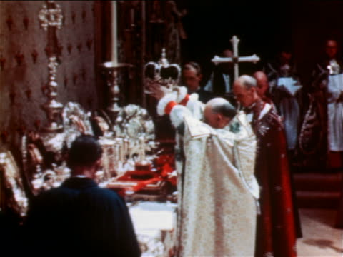 Archbishop lifting crown above head in Queen Elizabeth II coronation ceremony / documentary