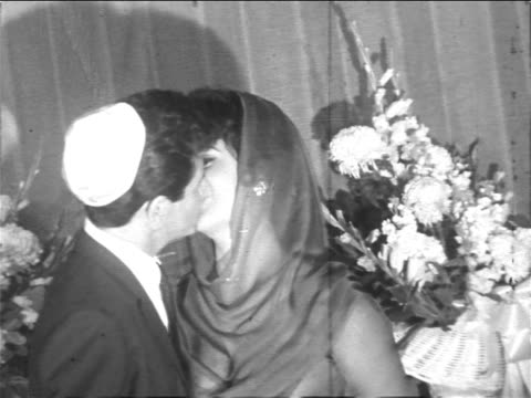 vídeos y material grabado en eventos de stock de elizabeth taylor + eddie fisher in yarmulke kissing after civil ceremony / newsreel - pareja de mediana edad