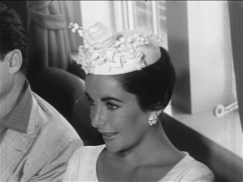 close up elizabeth taylor with hat sitting next to mike todd at press conference / newsreel - celebrities video stock e b–roll