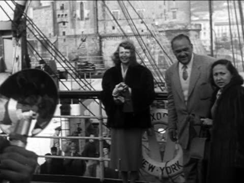 Rita Hayworth posing by dock railing smiling at media offscreen / Naples Italy / newsreel