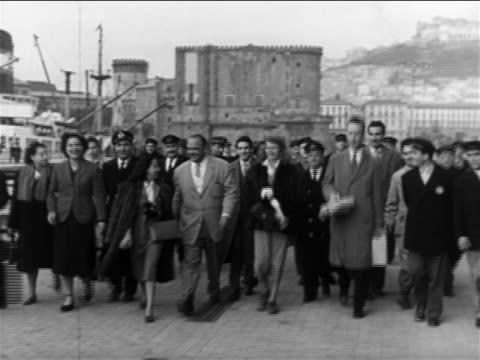 rita hayworth + entourage walking toward camera / naples, italy / newsreel - 毛皮のコート点の映像素材/bロール