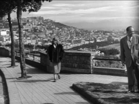 vídeos de stock e filmes b-roll de rita hayworth walking away from scenic view toward camera / naples, italy / newsreel - 1951
