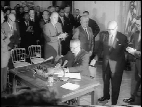 vídeos de stock, filmes e b-roll de b/w 1964 men surrounding president johnson at desk signing civil rights act / newsreel - 1964