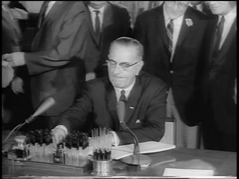 stockvideo's en b-roll-footage met president lyndon johnson at desk signing civil rights act / others behind him / newsreel - 1964