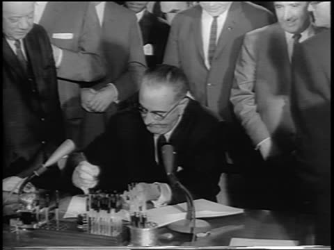 vidéos et rushes de president johnson signing civil rights act at desk surrounded by men / newsreel - 1964