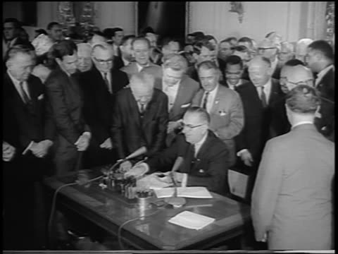 vídeos de stock, filmes e b-roll de b/w 1964 men watching as president lyndon johnson signs civil rights act at desk / newsreel - 1964