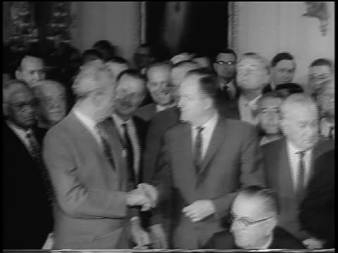 pan crowd of government officials / humphrey shakes hands with dirksen / johnson sitting - アメリカ黒人の歴史点の映像素材/bロール