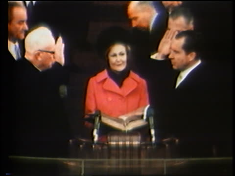 Pat Nixon holding Bible as Richard Nixon is sworn in as president / Johnson watching