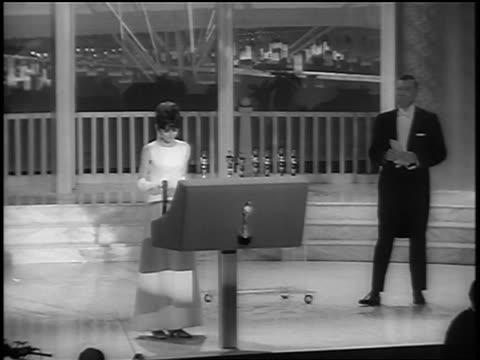 audrey hepburn at podium presenting award at academy awards / newsreel - audrey hepburn stock-videos und b-roll-filmmaterial