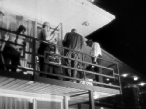b/w 1968 low angle police on balcony at motel at night where ml king was assassinated / newsreel - 1968年点の映像素材/bロール