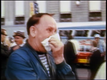 vidéos et rushes de middle-aged man covering face during tear-gassing at anti-war protest / chicago / newsreel - 1968