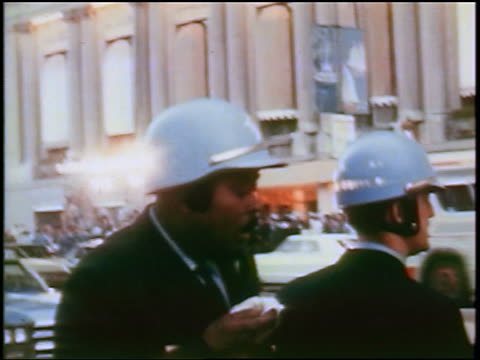 1968 police coughing during teargassing at antiwar protest / crowd in background / Chicago / newsreel