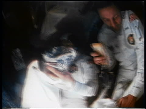 1970 two astronauts putting objects into bags in space capsule / Apollo 13 / documentary