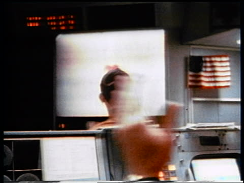 VIEW men in mission control clapping while watching descent of Apollo 13 capsule
