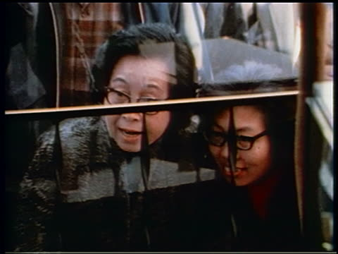 1970 zoom out from two Asian women to crowd on sidewalk watching TVs thru window