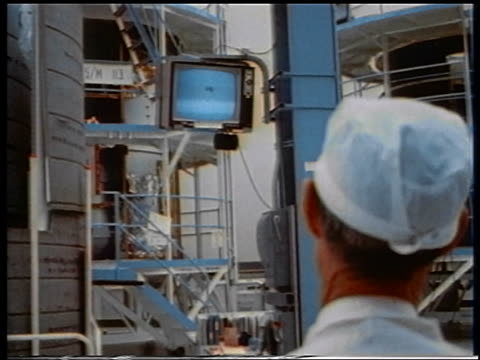 VIEW man in paper hat watching television in spacecraft assembly room
