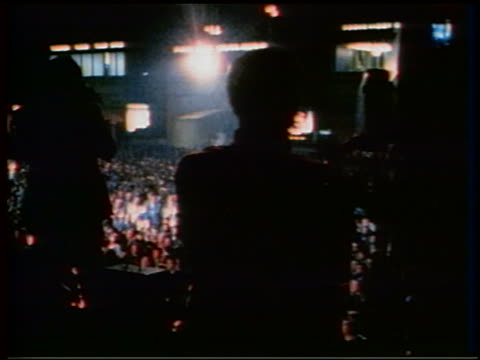 1970 zoom in PAN seated audience clapping / silhouetted camera crew in foreground / watching Apollo 13