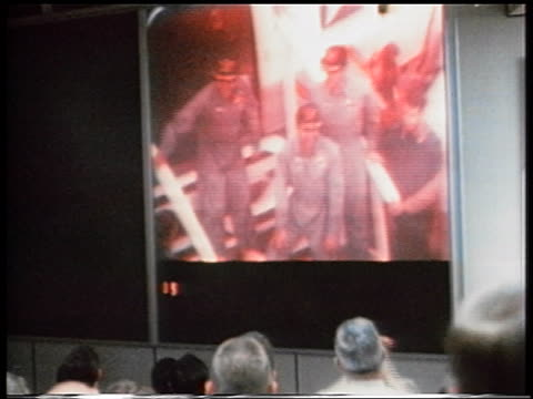 Apollo 13 astronauts on large monitor in mission control with people clapping in foreground