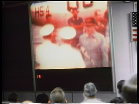 Apollo 13 astronauts greeted by naval officers on monitor in mission control after landing