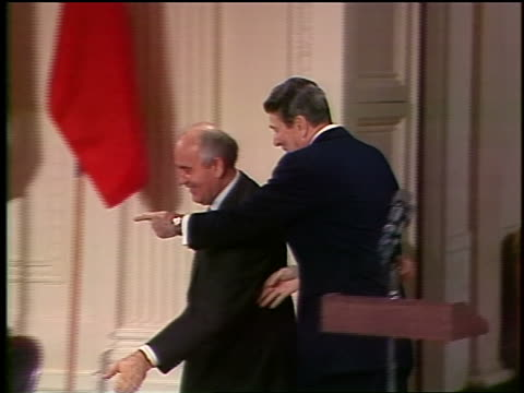 reagan + gorbachev clap, shake hands + sign intermediate range nuclear forces treaty - guerra fredda video stock e b–roll