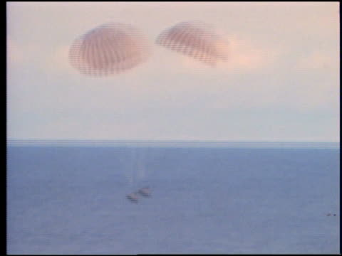 wide shot AERIAL of space capsule with parachutes splashing down / Apollo 13