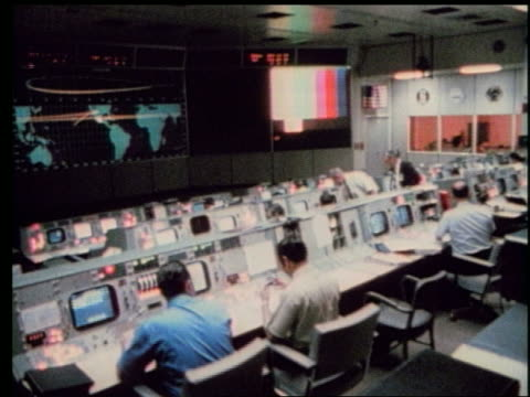 high angle wide shot of men at control panel in Mission Control