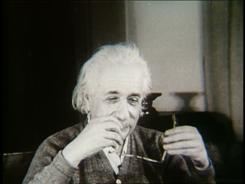 B/W Albert Einstein putting on eyeglasses