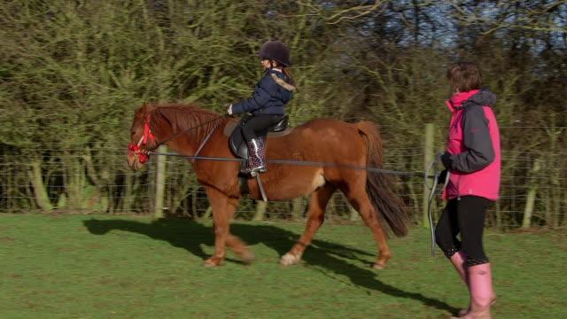 vídeos de stock, filmes e b-roll de learning to ride a pony - montar um animal