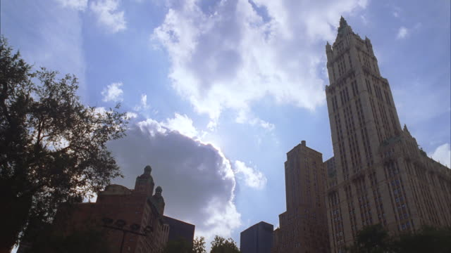 ua woolworth building, new york city, with sun behind clouds - woolworth building stock videos & royalty-free footage