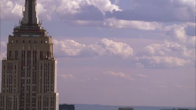 close on upper portion of empire state buidling w/clouds passing by - empire state building video stock e b–roll