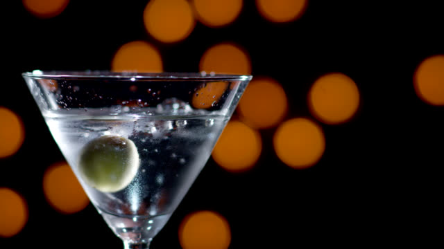 martini with olive dropped-slow motion - martini stock videos & royalty-free footage