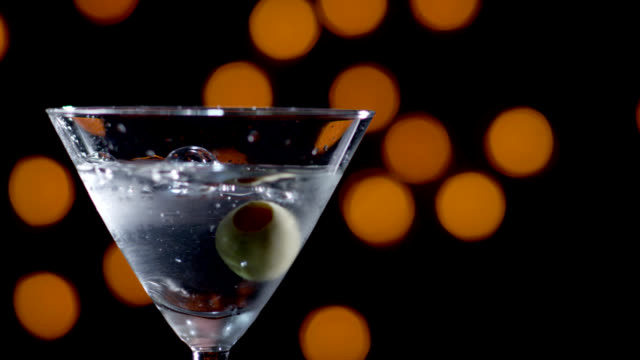 martini with olive dropped-slow motion - martini glass stock videos and b-roll footage