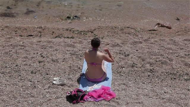 woman throwing pebbles in sea - asciugamano video stock e b–roll