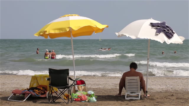 yellow and white parasols in wind - beach umbrella stock videos and b-roll footage