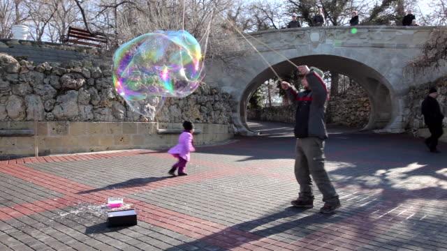 man creates childrens bubbles with rods washing up liquid sevastopol crimea ukraine - sevastopol crimea stock videos and b-roll footage