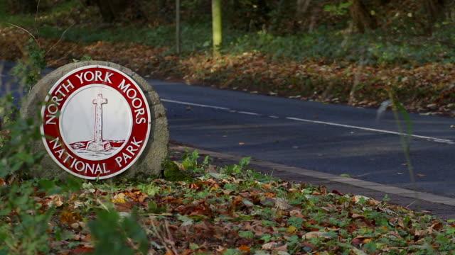 vídeos de stock e filmes b-roll de north yorkshire moors national park road sign on round stone - scarborough reino unido