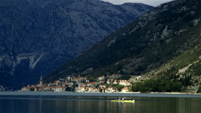 canoeing on kotor bay perast town and mountain range - perast stock videos and b-roll footage